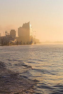 Germany, Hamburg, Silhouette of Elbphilharmonie seen across river at sunrise - p300m2160559 by Irina Heß