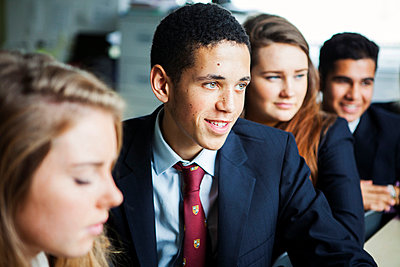 Teenage schoolchildren sitting at desks - p429m873069 by Nancy Honey