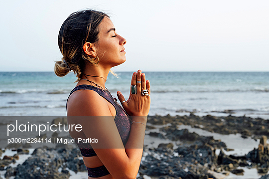 Young woman with hands clasped meditating at beach - p300m2294114 by Miguel Partido