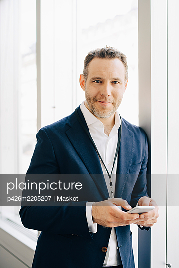 Portrait of entrepreneur with smart phone standing at workplace - p426m2205207 by Maskot
