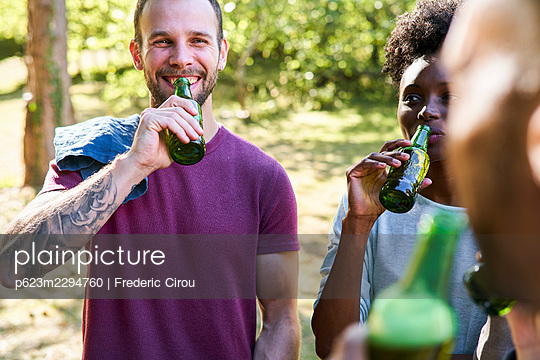 Young friends drinking beer while standing in park - p623m2294760 by Frederic Cirou