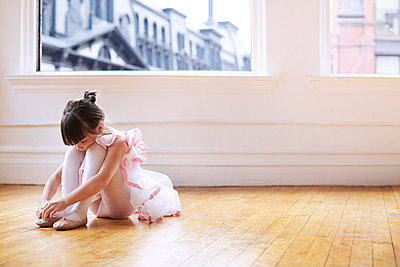 Girl wearing ballet shoes while sitting on hardwood floor in studio - p1166m1097601f by Cavan Images