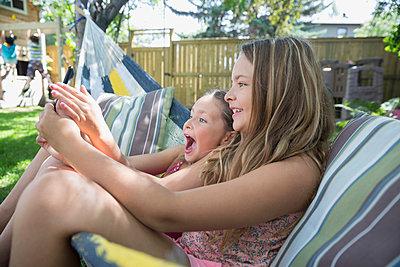 Playful girls taking selfie in hammock in backyard - p1192m1183941 by Hero Images