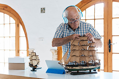 Senior man wearing headphones working on model ship on table with tablet - p300m1470163 by Josep Rovirosa