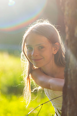 Portrait of smiling girl in nature at backlight - p300m2062744 by Sandra Roesch