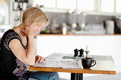 Adult woman sitting alone in kitchen and reading newspaper - p312m1551940 by Johner Images