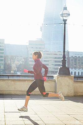 Woman running on urban bridge - p429m800815f by Moof