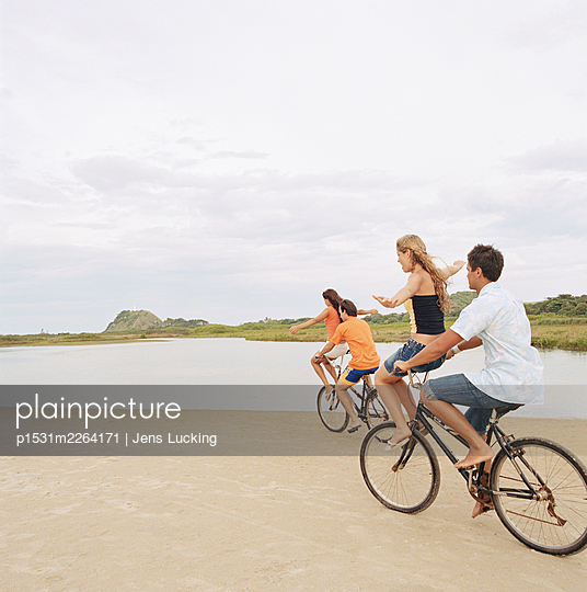 Two Young Men Cycling With Two Young Women Balancing On Handlebars - p1531m2264171 by Jens Lucking