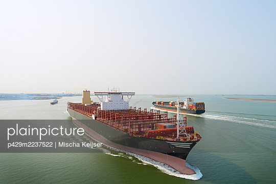 A 400m long container ship sails to the port of Antwerp, passing smaller ships. The ship not fully loaded, due to coronavirus - p429m2237522 by Mischa Keijser