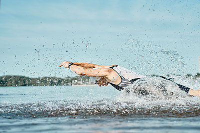 Side view of young swimmer man in rubber cap jumping into river - p1630m2196900 by Sergey Mironov