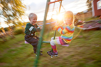 Boy and girl swinging, Norrbotten, Sweden - p312m926982f by Fredrik Ludvigsson
