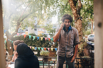 Young man talking on mobile phone while standing in balcony during party - p426m2046228 by Maskot