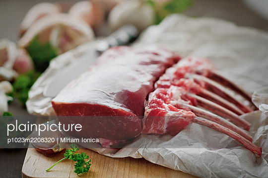 Fresh rack of raw lamb on cutting board - p1023m2208320 by Miriam Ionica
