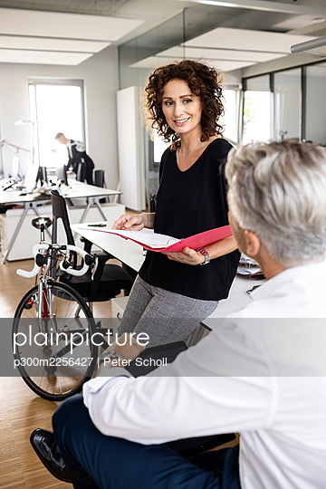 Business people having discussion while working with colleague in background at office - p300m2256427 by Peter Scholl