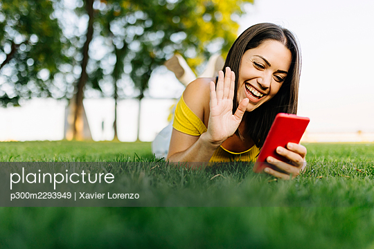Cheerful woman waving on video call through smart phone while lying in park - p300m2293949 by Xavier Lorenzo