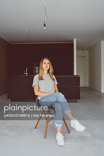 Nachdenkliche junge Frau in neuer Wohnung - p432m2199814 von mia takahara