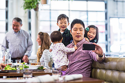 Father taking selfie with children while sitting with family in restaurant - p1166m1423414 by Cavan Images