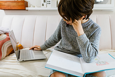 Child sitting on sofa looking at laptop white sketching on a book - p1166m2224162 by Cavan Images