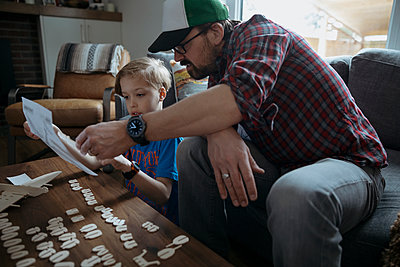 Father and son assembling model airplane, reading directions - p1192m1567341 by Hero Images
