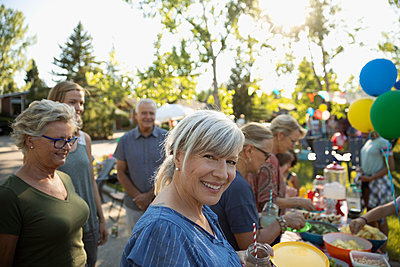 Portrait smiling senior woman eating, enjoying summer neighborhood block party at park - p1192m2017090 by Hero Images