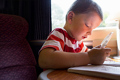 Close up of young boy with puzzle book on train - p429m824248f by Gary John Norman