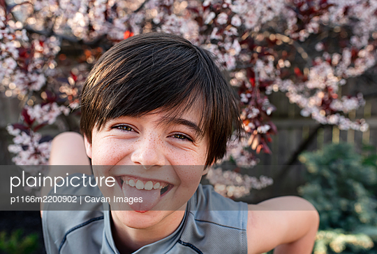 Portrait of happy young boy sticking tongue out outdoors in a garden. - p1166m2200902 by Cavan Images