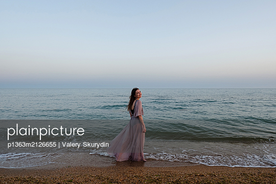 Woman standing on beach - p1363m2126655 by Valery Skurydin