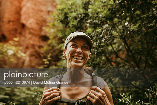 Smiling woman explorer standing in forest - p300m2213974 by David Molina Grande