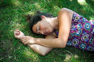 Young woman sleeping in the grass - p1007m854275 by Tilby Vattard