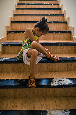 Little girl sitts on stairs tying up her sandals - p1118m2151093 by Tarik Yaici