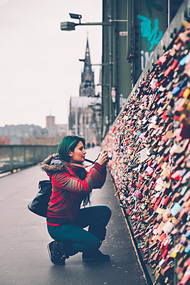 Germany, Cologne, woman taking picture of love locks at Hohenzollern Bridge - p300m1176184 by Retales Botijero