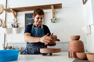 Smiling female potter working with brown clay at ceramic store - p300m2240350 by Ezequiel Giménez