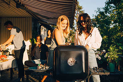 Female friends talking while grilling food on barbecue in dinner party - p426m2097391 by Maskot