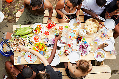 High angle view of friends enjoying backyard barbecue - p555m1409852 by Granger Wootz