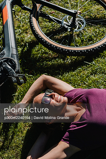 Smiling woman resting while lying on grass by mountain bike at park - p300m2240164 von David Molina Grande