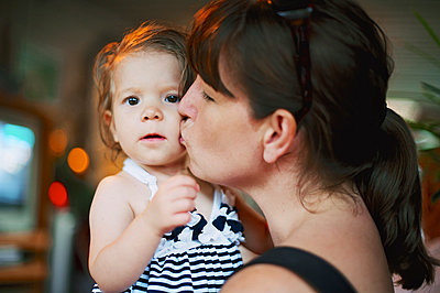 mom kissing baby girl - p1169m1032725 by Tytia Habing
