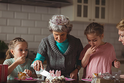 Grandmother celebrating her birthday with her family at home - p1315m1566646 by Wavebreak