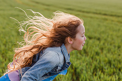 Girl with blowing hair running on a field - p300m1416823 by Nicole Matthews