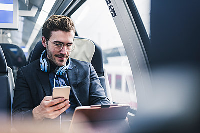 Businessman in train with cell phone, headphones and tablet - p300m1563030 by Uwe Umstätter