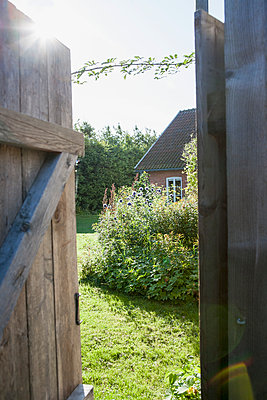 Open door with house in background - p312m1121481f by Lina Karna Kippel