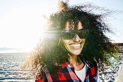 Portrait of smiling Hispanic woman at beach - p555m1303380 by Peathegee Inc