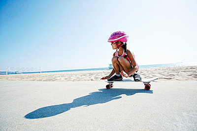 Mixed race girl riding skateboard at beach - p555m1305538 by Peathegee Inc
