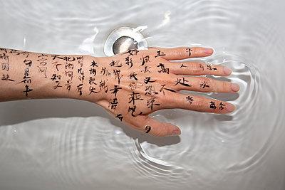 Tattooed hand touching fluid - p817m2179093 by Daniel K Schweitzer