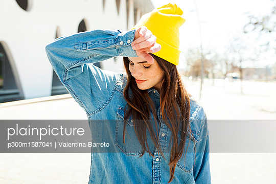 Spain, Barcelona, young woman wearing yellow cap and denim shirt - p300m1587041 von Valentina Barreto