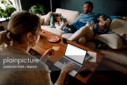 Mother online shopping while man and daughters using various technologies in living room - p426m2074359 by Maskot