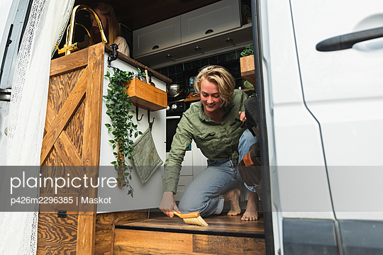 Young woman cleaning motor home - p426m2296385 by Maskot