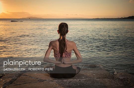 Woman practising yoga at seaside - p429m2091234 by ROBERTO PERI