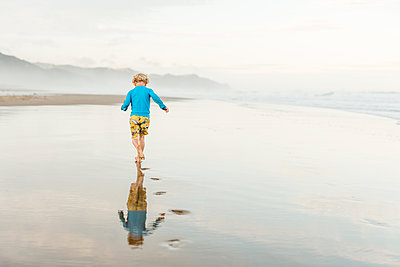 Back view of child running on a beach with footprints - p1166m2129633 by Cavan Images