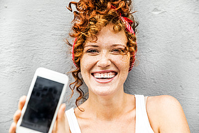 Happy redheaded woman showing cell phone - p300m1505514 by Jo Kirchherr
