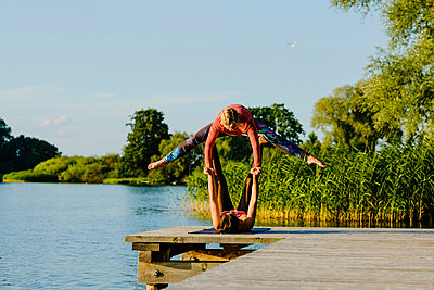 Women practicing acro yoga on sunny lakeside dock - p301m2075552 by Sven Hagolani